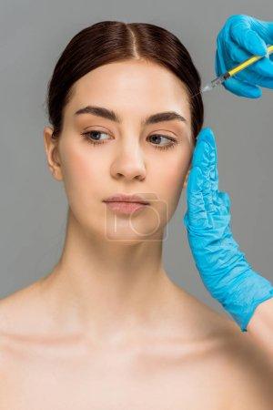 Foto de Vista recortada del cirujano plástico haciendo la inyección de belleza a la atractiva mujer desnuda aislada en gris - Imagen libre de derechos