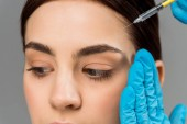 cropped view of plastic surgeon holding syringe near brunette woman isolated on grey