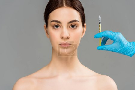 Photo for Cropped view of plastic surgeon holding syringe near naked pretty woman isolated on grey - Royalty Free Image