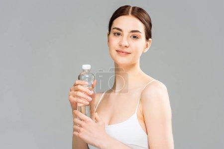 Photo pour Jeune femme heureux retenant la bouteille avec l'eau d'isolement sur le gris - image libre de droit
