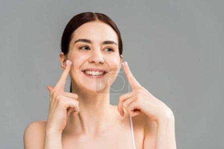 Foto de Chica morena alegre con crema facial en los dedos aislados en gris - Imagen libre de derechos