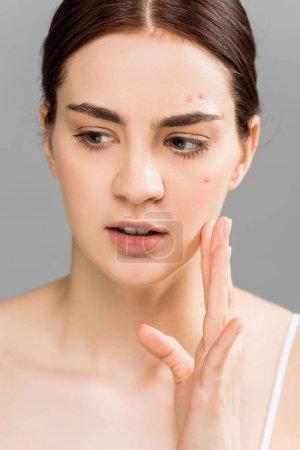 Photo pour Jeune femme brune attirante avec le visage touchant d'acné d'ondulant sur le gris - image libre de droit