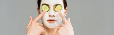 Photo pour Tir panoramique de jeune femme avec le masque d'argile et les concombres sur le visage isolé sur le gris - image libre de droit