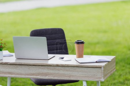 Photo pour Office table with laptop, coffee to go, notebook and smartphone near office chair in park - image libre de droit