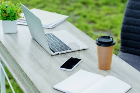 Photo for Selective focus of office table with laptop, coffee to go, notebook and smartphone near office chair in park - Royalty Free Image