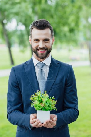 Photo for Young handsome businessman with plant in flowerpot standing in park - Royalty Free Image