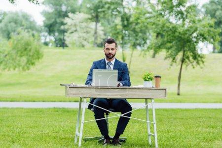 Foto de Apuesto joven hombre de negocios en ropa formal usando computadora portátil, sentado a la mesa en el parque y mirando a la cámara - Imagen libre de derechos