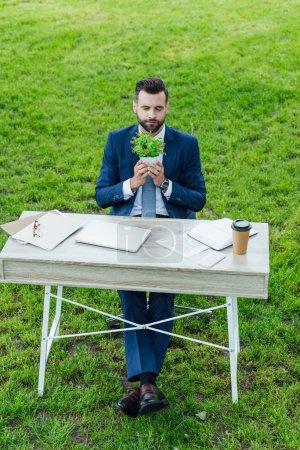Photo pour Vue d'angle élevé de la jeune usine de fixation d'homme d'affaires dans le pot de fleur et s'asseyant derrière la table avec l'ordinateur portatif, les cahiers et le café pour aller - image libre de droit