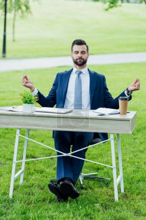 front view of handsome young businessman in formal wear meditating while sitting at table with various office stuff in park