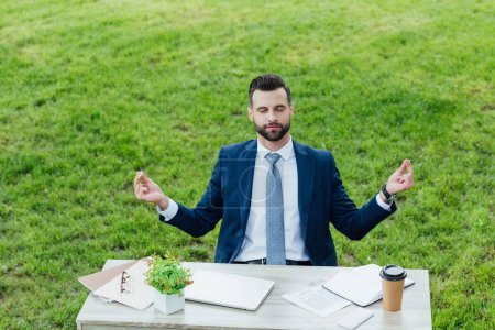 Photo for Handsome young businessman meditating while sitting in park behind table - Royalty Free Image