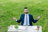 """Постер, картина, фотообои """"красивый молодой бизнесмен медитирует, сидя в парке за столом"""""""