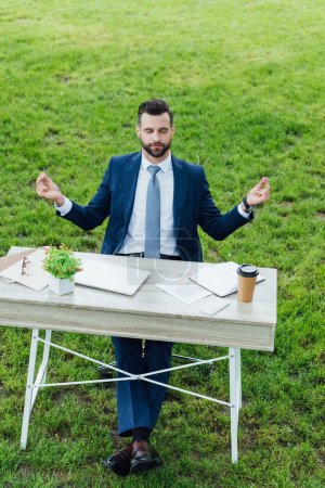 full length view of handsome young businessman in formal wear meditating while sitting at table with various office stuff in park
