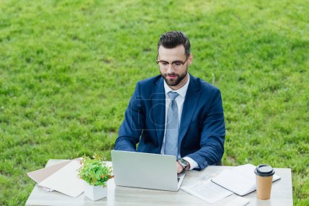 Photo for Young businessman in formal wear using laptop while sitting in park behind white office table - Royalty Free Image