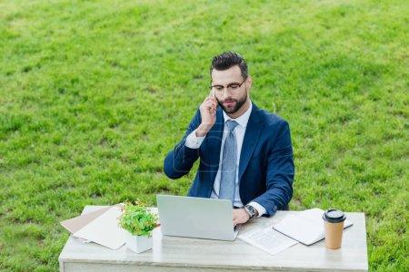 Photo pour Jeune homme d'affaires dans l'usure formelle utilisant l'ordinateur portatif et parlant sur le smartphone tout en s'asseyant dans le stationnement derrière la table de bureau - image libre de droit