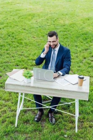Photo pour Jeune homme d'affaires dans l'usure formelle utilisant l'ordinateur portatif, souriant et parlant sur le smartphone tout en s'asseyant dans le stationnement derrière la table de bureau - image libre de droit