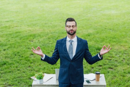 Photo pour Young businessman in formal wear meditating near table with various office stuff in park - image libre de droit