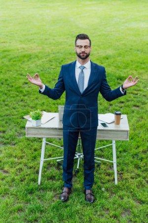 Photo pour Vue pleine longueur de jeune homme d'affaires en tenue de cérémonie méditant debout près de la table dans le parc - image libre de droit