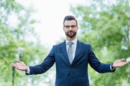 Photo pour Vue de face de jeune homme d'affaires gesticulant tout en se tenant dans le parc - image libre de droit