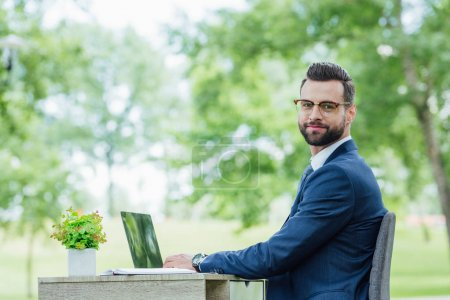Photo for Young businessman sitting behind table and looking at camera while using laptop - Royalty Free Image