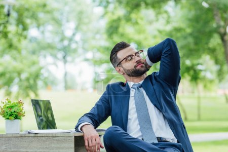 Photo pour Young businessman in formal wear sitting at table with laptop, plant and notebook and relaxing in park - image libre de droit