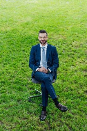 Photo pour Vue d'angle élevé de jeune homme d'affaires heureux s'asseyant dans la présidence de bureau dans le stationnement et loooking à l'appareil-photo - image libre de droit