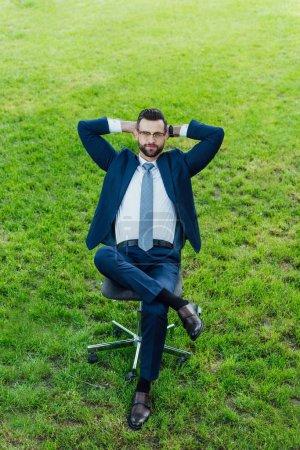 Photo pour Vue d'angle élevé de l'homme d'affaires s'asseyant dans la présidence de bureau dans le stationnement avec les décalages croisés et les bras derrière la tête - image libre de droit