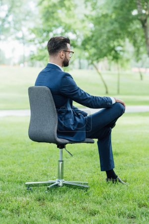 Photo for Young businessman sitting in office chair in park - Royalty Free Image