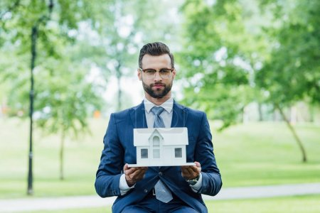 Photo for Young businessman holding white house layout and looking at camera while sitting in park - Royalty Free Image