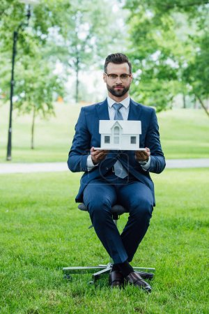 Photo pour Full length view of young man holding white house layout and looking at camera while sitting in park - image libre de droit