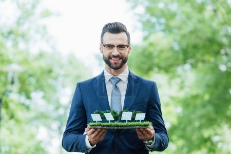 Foto de Young businessman holding park layout with sun batteries, smiling and looking at camera while standing in park - Imagen libre de derechos