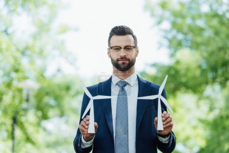 Photo for Young businessman holding windmills layout and looking at camera while standing in park - Royalty Free Image