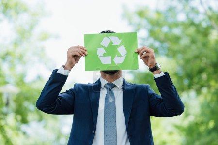 joven cubriendo la cara con la tarjeta de muestra de reciclaje mientras está de pie en el parque