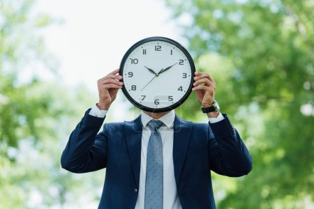 young man covering face with clock while standing in park