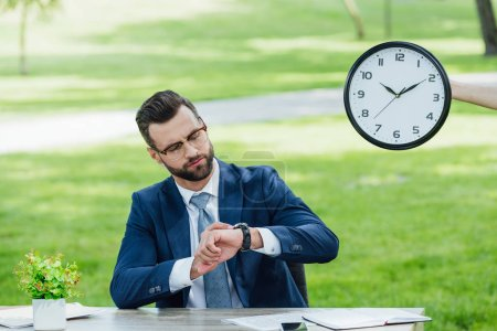 Photo pour Businessman sitting at table with plant in park and looking at watch - image libre de droit