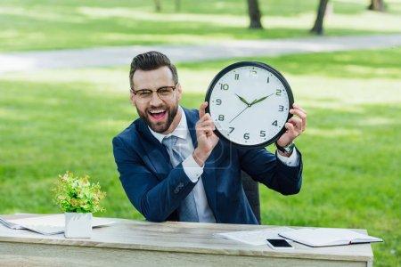 Photo pour Homme d'affaires s'asseyant derrière la table avec le pot de fleur, le smartphone et les cahiers, retenant l'horloge et regardant l'appareil-photo - image libre de droit