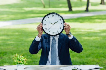 Photo for Businessman sitting behind table with plant and notebooks and covering face with clock - Royalty Free Image