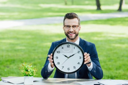 Photo pour Homme d'affaires s'asseyant derrière la table avec l'usine et les cahiers, souriant, regardant l'appareil-photo et tenant l'horloge - image libre de droit