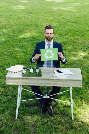Photo for High angle view of young businessman sitting at table with windmills layout, holding card with recycle sign and looking at camera - Royalty Free Image