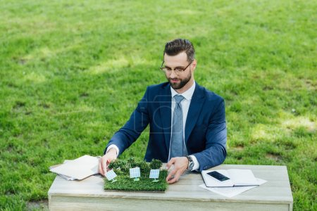Photo pour Businessman putting layout with sun batteries on table with notebooks and smartphone while sitting in office chair in park - image libre de droit