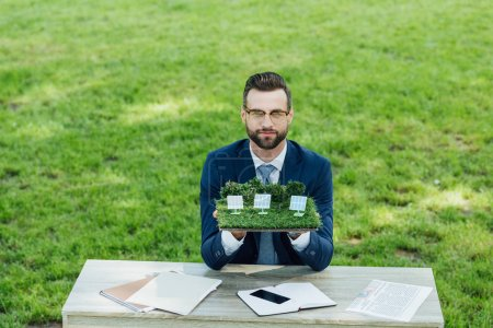 Photo for Businessman holding layout with sun batteries on table with notebooks and smartphone while sitting in office chair in park - Royalty Free Image