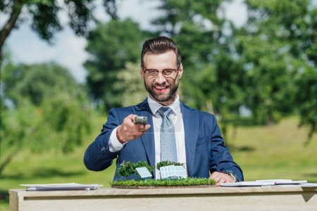 Photo for Young businessman with glasses sitting at table with sun batteries layout, looking at camera, smiling and presenting control panel - Royalty Free Image