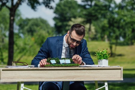 Photo for Young businessman in sunglasses sitting at table with sun batteries layout and flowerpot with plant - Royalty Free Image