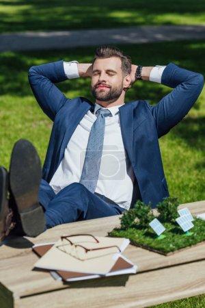 Photo pour Jeune homme d'affaires détendant tout en s'asseyant à la table avec la disposition de batteries de soleil, des verres et des noteboks, les décalages croisés et mettent des mains derrière la tête - image libre de droit