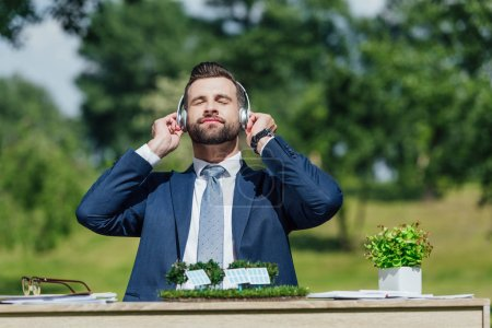 Foto de Young businessman sitting at table with sun batteries layout and flowerpot, relaxing while listening to music with headphones - Imagen libre de derechos