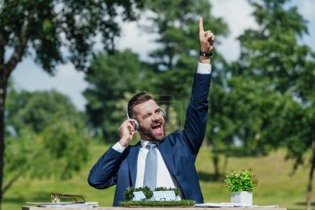 Photo pour Excited young businessman sitting at table with sun batteries layout and flowerpot, listening to music with headphones and putting hand in air - image libre de droit