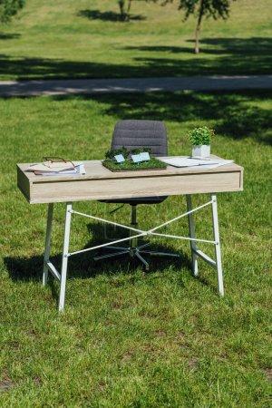 mesa con el diseño de baterías de sol, flowepot, cuadernos y vasos cerca de la silla de oficina negro en el parque