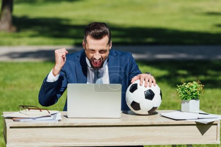 Photo for Young businessman sitting at table with laptop, flowerpot and glasses, watching football, cheering on team and holding soccer ball - Royalty Free Image