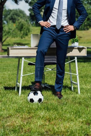 Photo for Cropped view of businessman standing with leg on soccer ball near table in park with hands on hips - Royalty Free Image