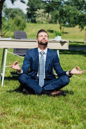 Photo pour Homme d'affaires s'asseyant et méditant sur l'herbe près de la table en stationnement - image libre de droit
