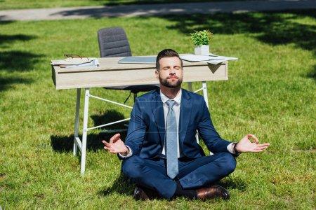 Photo pour Homme d'affaires s'asseyant sur l'herbe et méditant près de la table en stationnement - image libre de droit
